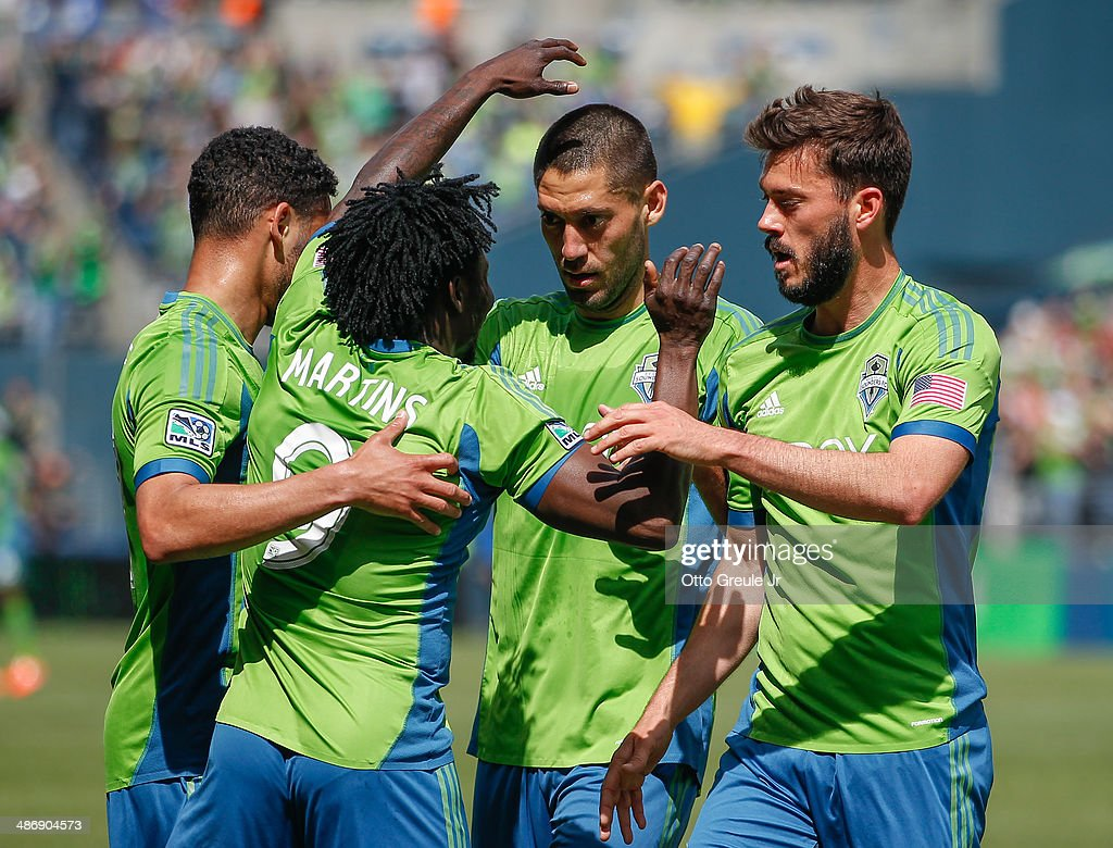 Obafemi Martins #9 of the Seattle Sounders FC is congratulated by Lamar Neagle #27 (far left), Clint Dempsey #2, and Brad Evans #3 after scoring a goal in the second half against the Colorado Rapids at CenturyLink Field on April 26, 2014 in Seattle, Washington. The Sounders defeated the Rapids 4-1.