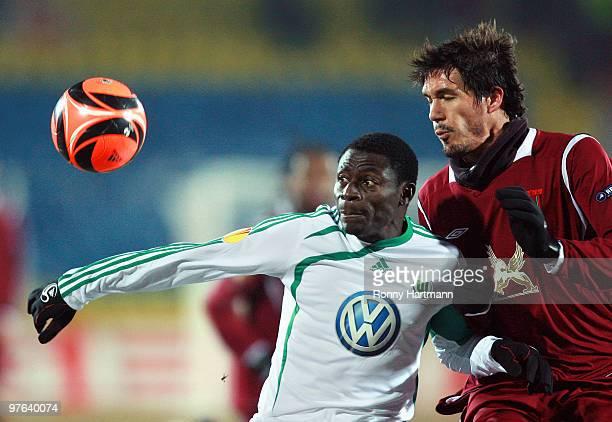 Obafemi Martins of Wolfsburg battles for the ball with Cesar Navas of Kazan during the UEFA Europa League round of 16 first leg match between Rubin...