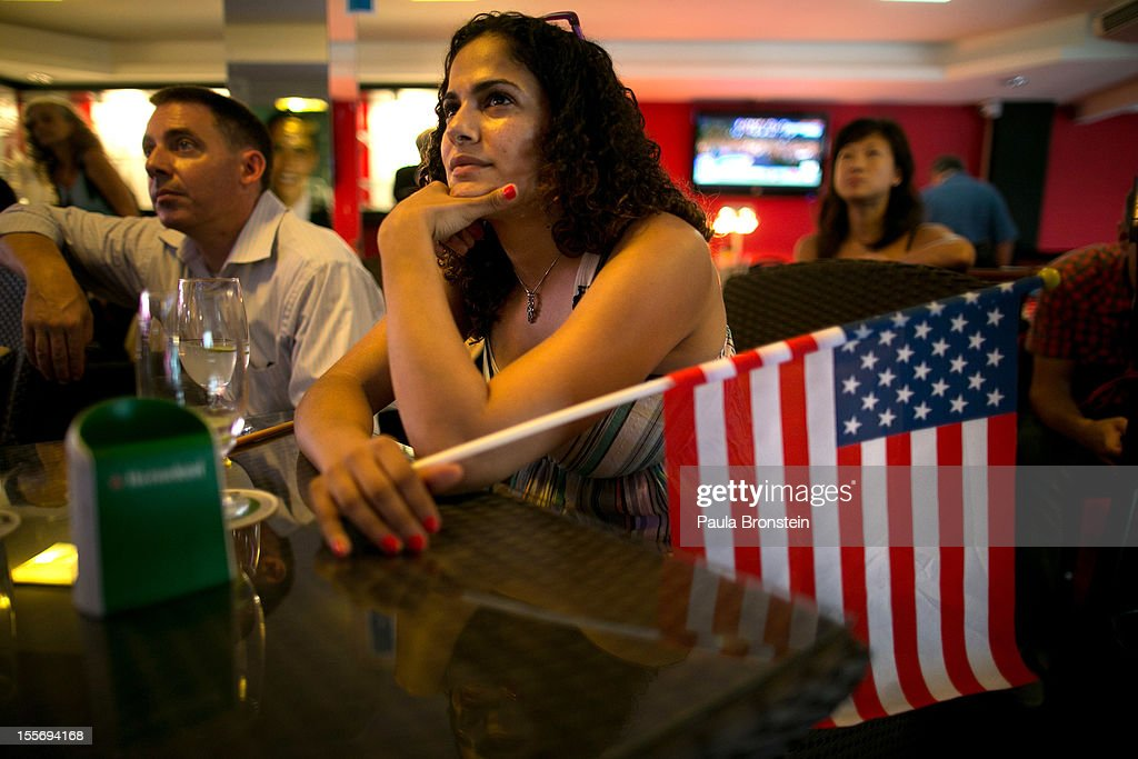 Obama supporter Sara Elsayed from North Carolina listens to President Obama's victory speech at the Deomcrats Abroad gathering November 7, 2012 in Bangkok, Thailand. Obama won with 303 electoral votes to Romney's 206 with Florida votes still not included in the total.