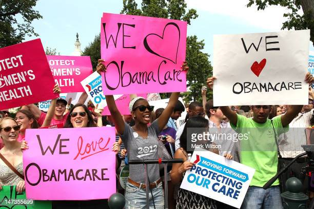 Obamacare supporters react to the US Supreme Court decision to uphold President Obama's health care law on June 28 2012 in Washington DC Today the...
