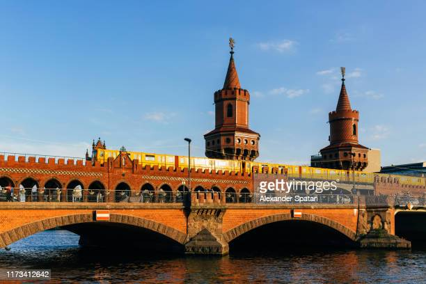 oberbaum bridge (oberbraumbrücke) and yellow metro train on a sunny day with blue sky, berlin, germany - フリードリッヒハイン ストックフォトと画像