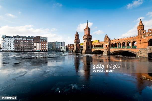 oberbaum bridge over frozen spree river against sky - friedrichshain stock photos and pictures