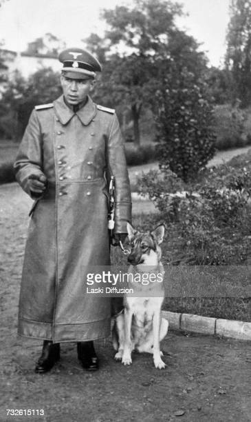 Obersturmführer, Eduard Karl Schmidt with an alsatian dog, 1942. A photo from an album documenting German atrocities in occupied Poland during World...