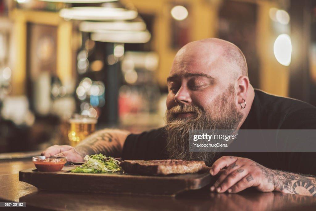 Fettleibige männliche genießen gegrilltes Fleisch in der Kneipe : Stock-Foto