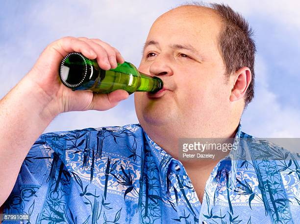 Obese man drinking beer against sky.