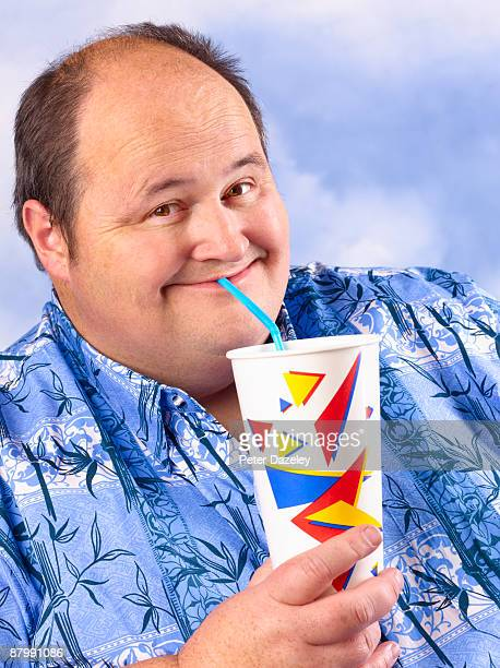 Obese man drinking cola/ soda fizzy drink.