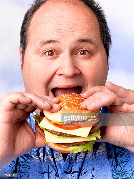 Obese man eating hamburger.