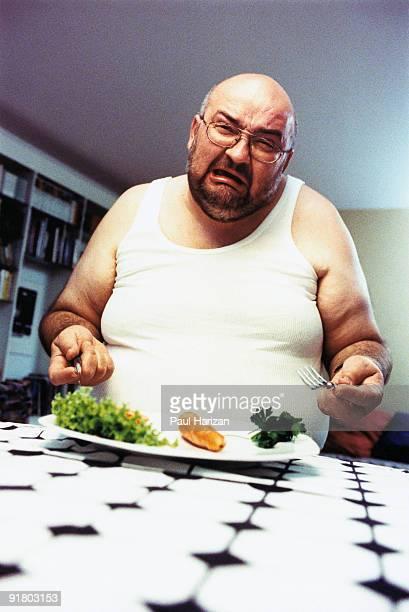 Obese man eating vegetables