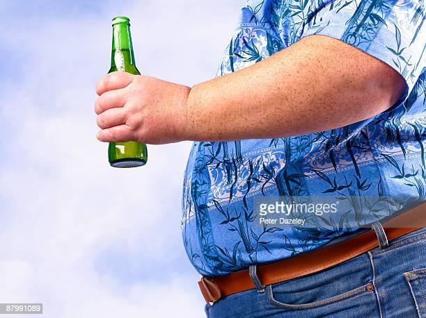 Obese man holding beer bottle against sky.