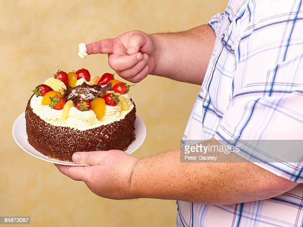 obese man holding fruit gâteaux with cream on - bulimia fotografías e imágenes de stock