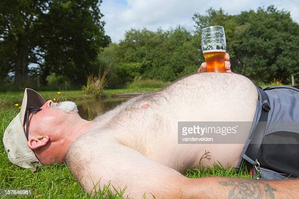 Obese Man With A Glass Of Beer Sunbathing