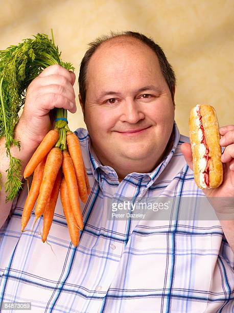 obese man with cream cake and carrots. - chubby men stock photos and pictures