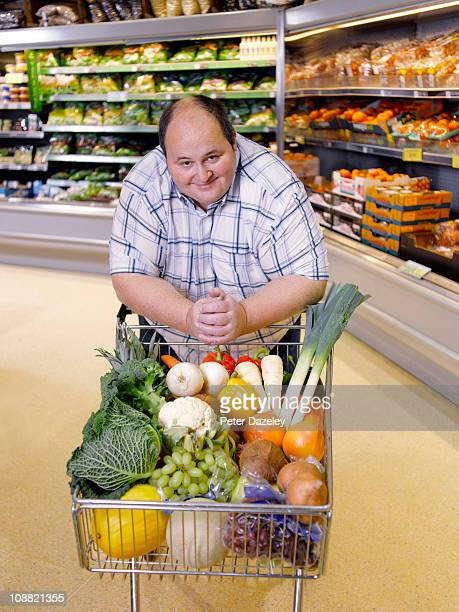 Obese man with healthy food in supermarket