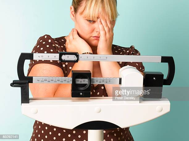 obese teenager on scales - fat girls stock photos and pictures