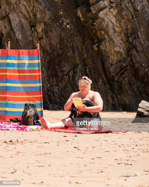 obese woman eating from container. caswell bay beach, near swansea, on the gower peninsular, south wales. june - hot women pics stock pictures, royalty-free photos & images