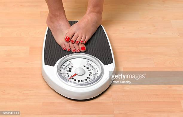 Obese woman weighing herself