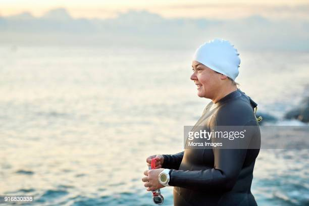 Obese woman with swimming goggles by sea at beach