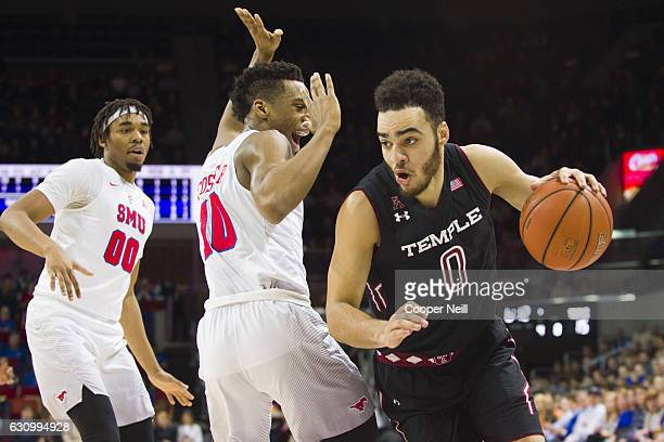 Obi Enechionyia of the Temple Owls brings the ball up court against Jarrey Foster and Ben Moore of the SMU Mustangs during a basketball game on...