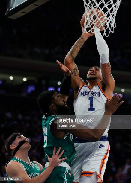 Obi Toppin of the New York Knicks goes to the basket as Payton Pritchard and Jaylen Brown of the Boston Celtics defend during the first half at...