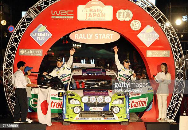 Finnish driver Mikko Hirvonen and codriver Jarmo Lehtinen wave to fans from their Ford Focus RS WRC 2006 during the ceremonial start for the Japanese...