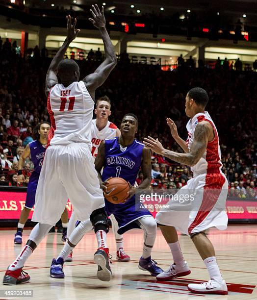 Obij Aget of the New Mexico Lobos blocks the shot as Demetrius Walker of the Grand Canyon Antelopes stops to shoot during the Monday night game at...