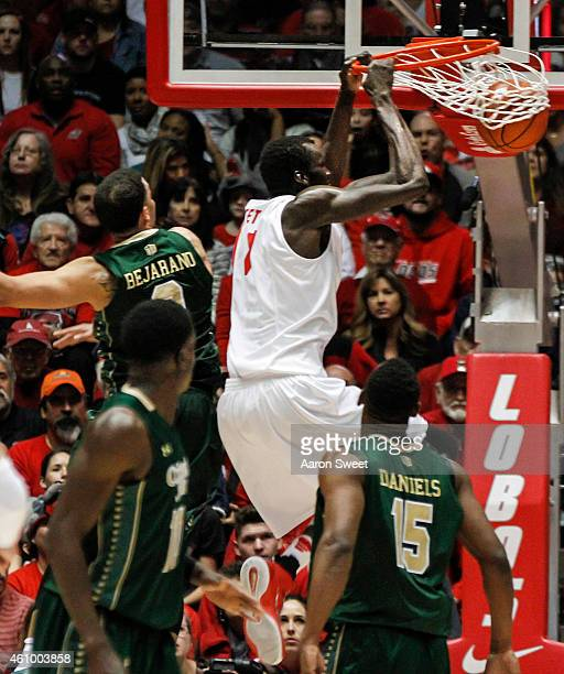 Obij Aget of the New Mexico Lobos dunks the ball as Daniel Bejarano of the Colorado State Rams defends during their game at The WisePies Arena on...