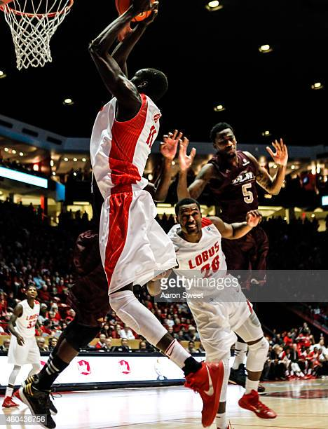 Obij Aget of the New Mexico Lobos jumps to shoot as teammate Sam Logwood defends against Jamaal Samuel of the LouisianaMonroe Warhawks during their...