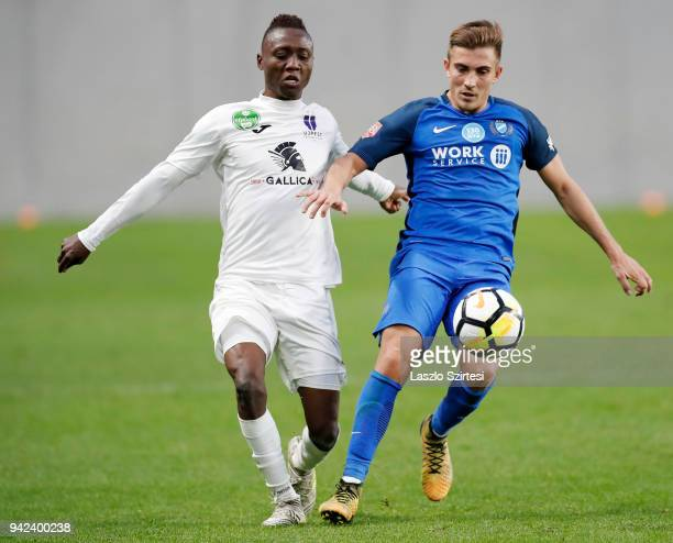 Obinna Nwobodo of Ujpest FC competes for the ball with David Jakab of MTK Budapest during the Hungarian Cup Quarter Final 2nd Leg match between MTK...