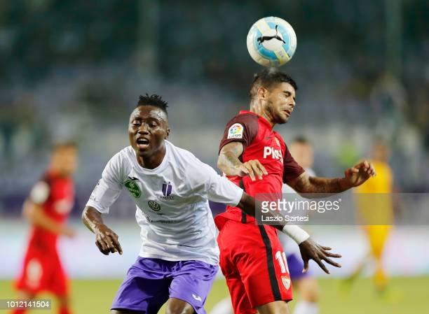Obinna Nwobodo of Ujpest FC competes for the ball with Ever Banega of Sevilla FC during the UEFA Europa League Second Qualifying Round 2nd Leg match...