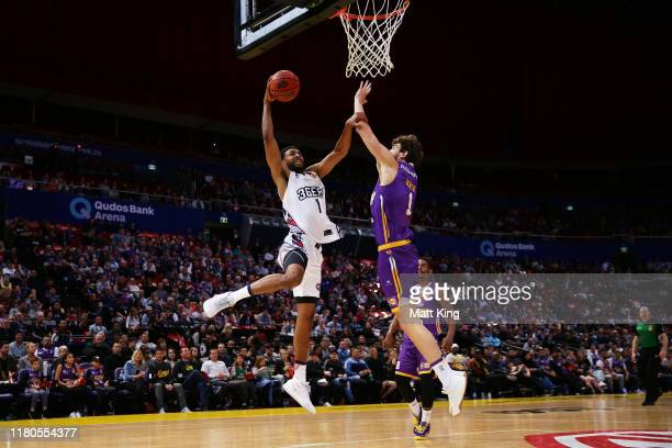 Obiri Kyei of the 36ers slam dunks under pressure from Jordan Hunter of the Kings during the round two NBL match between the Sydney Kings and the...