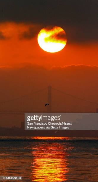 {object name} The sunrise finally broke through dense morning cloud cover over the Bay Bridge making a golden path of sun light across the bay to...