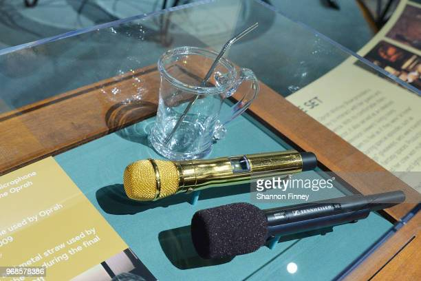 Objects from the set of The Oprah Winfrey Show including a glass mug and metal straw used by Ms Winfrey a gold microphone and a wireless microphone...