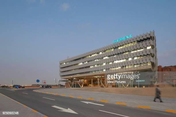 Oblique elevation with approach at dusk. Siemens Masdar, Abu Dhabi, United Arab Emirates. Architect: Sheppard Robson, 2014.