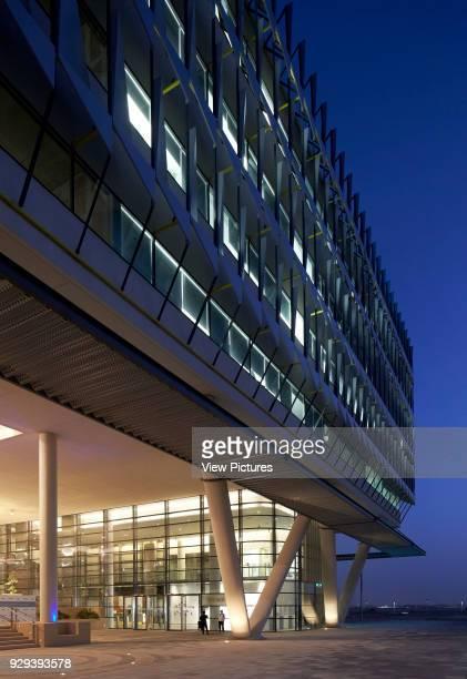 Oblique elevation with main entrance at dusk. Siemens Masdar, Abu Dhabi, United Arab Emirates. Architect: Sheppard Robson, 2014.
