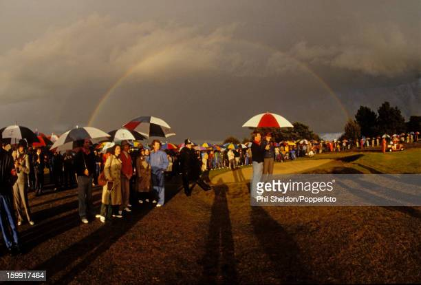 Oblivious to the rainbow behind them American golfers Jerry Pate Tom Watson and Ben Crenshaw with their wives shelter from a rainstorm during the...