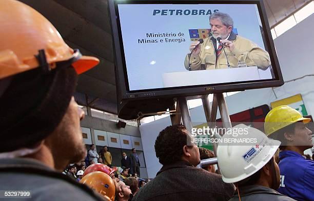 Obreros de la estatal petrolera brasilena Petrobras observan a Luiz Inacio Lula da Silvan presidente de Brasil durante un discurso en el Club de los...