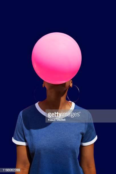 obscured face of woman blowing balloon - blasen stock-fotos und bilder