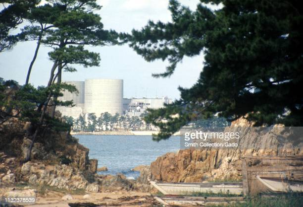 Obscured view of Mihama Nuclear Power Plant, with Nyunoura bay, pine trees, rocks, and fishing boats in the foreground, Mihama, Japan, 1970. Image...