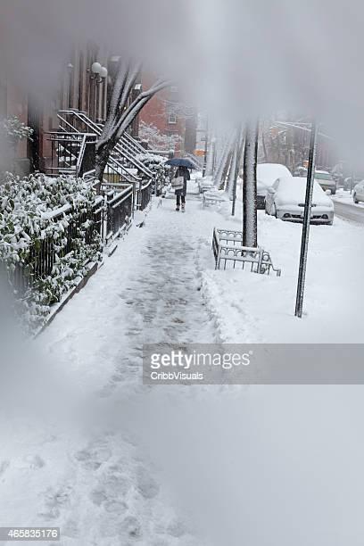 Obscured view woman walking along Brooklyn street in snow storm