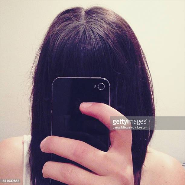 Obscured young woman clicking herself with camera phone