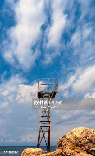 Observation Point At Beach Against Cloudy Sky During Sunny Day