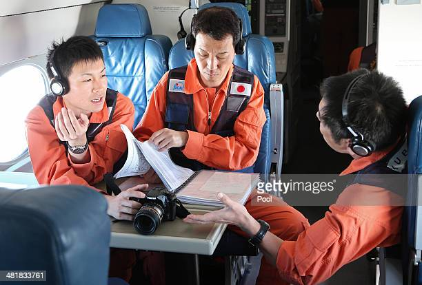 Observers on a Japan Coast Guard Gulfstream aircraft discuss their mission brief before they begin searching for wreckage and debris of missing...