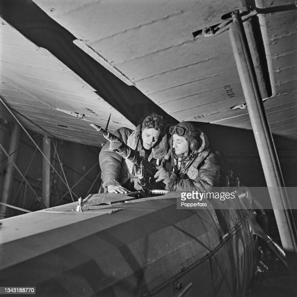 Observers test the Vickers machine gun mounted on to a Fairey Swordfish biplane torpedo bomber from the Royal Navy Fleet Air Arm aboard the aircraft...