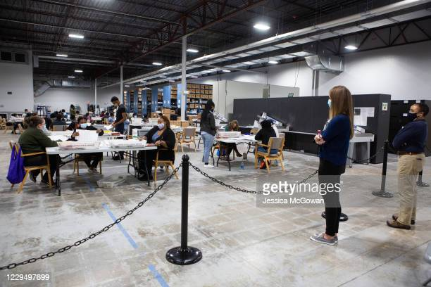Observers watch as Gwinnett County workers continue to process absentee and provisional ballots at the Gwinnett Voter Registrations and Elections...