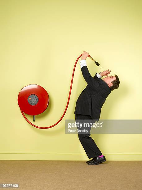 Obsessive business man cleaning fire hose