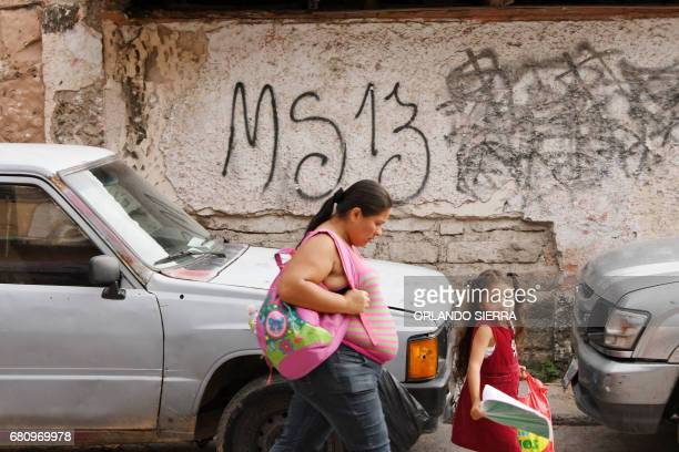 ocal residents pass by a grafitti made by the Mara Salvatrucha gang in the MS13controlled El Bosque neighborhood in Tegucigalpa on May 9 2017 The...