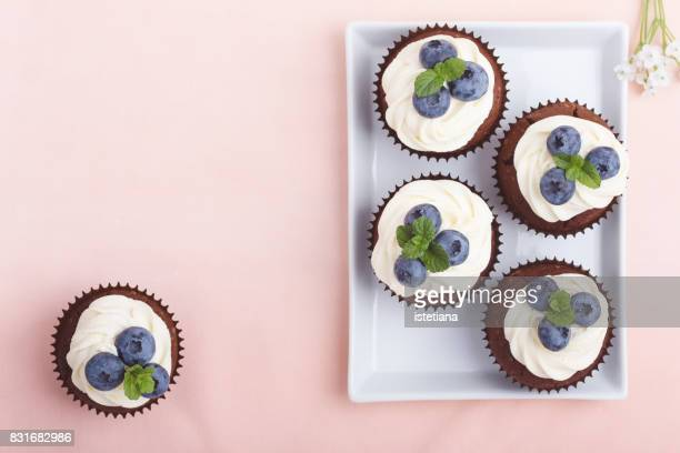 Occasions. Cream cheese  chocolate cupcakes on pink table