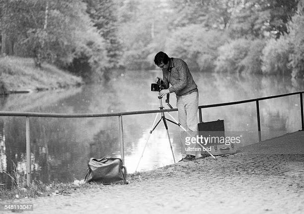 occupation professional photographer at work camera tripod camera holdall landscape lake aged 30 to 40 years Werner DAmberg Vils Upper Palatinate...