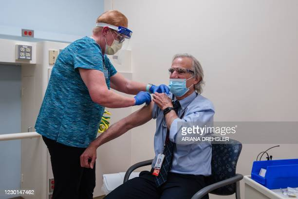 Occupational Health Nurse Maureen Finnegan gives Pfizer-BioNTech Covid-19 Vaccine shot to Medical Director of Infectious Diseases, Dr. John Bradley...