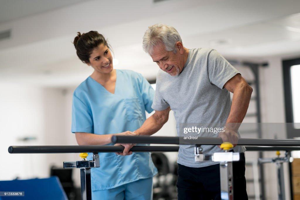 Terapeuta ocupacional y paciente mayor con barras paralelas para caminar : Foto de stock